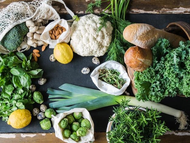 健康的な菜食主義の食材。様々なきれいな野菜、ハーブ、ナッツ、黒の背景にパン。プラスチックなしの市場からの製品。平らに置きます。