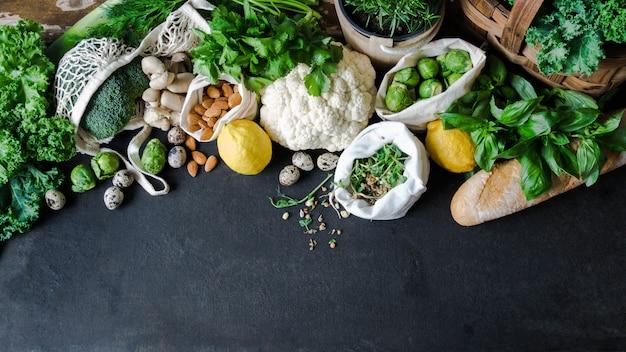 健康的な菜食主義の食材。様々なきれいな野菜、ハーブ、ナッツ、大理石の背景にパン。プラスチックなしの市場からの製品。平らに置きます。コピースペース