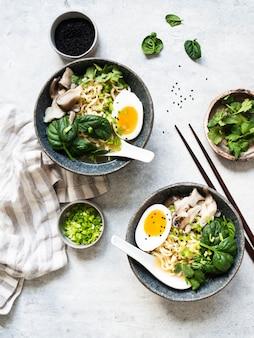 Вегетарианская мисо рамэн с грибами, сырым шпинатом и вареным яйцом в голубой миске на сером столе.