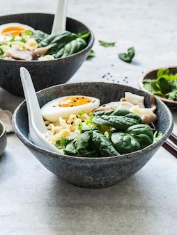 Вегетарианское мисо рамэн с грибами, сырым шпинатом и вареным яйцом в синей миске