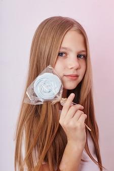 美しい少女の長い髪を食べるロリポップキャラメル