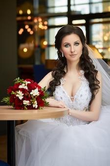 テーブルに座って花の花束を持つ花嫁