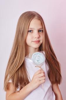 美しい少女のブロンドの髪は、ロリポップキャラメルを食べる