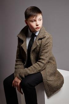 少年はコートシャツとネクタイのビジネスマンです。