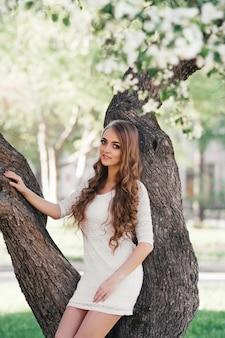 春の公園を歩いて美しいブロンドの女の子