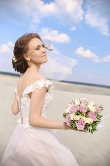 砂漠のダンスのウェディングドレスの女性の花嫁