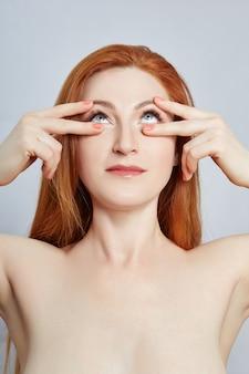 フェイシャルマッサージ、体操、マッサージライン、プラスチック製の口目と鼻をしている女性