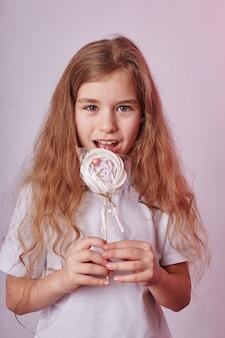 ブロンドの髪を持つ美しい少女は、陽気な笑みを浮かべて少女の手で棒に丸いキャラメル、ロリポップを食べる