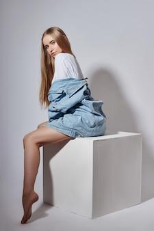 ファッション裸金髪の女の子は、スタジオのホワイトキューブに座っています。ファッションポーズ