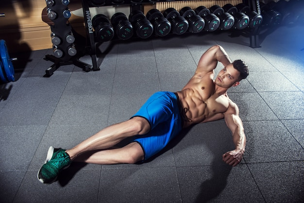 筋力トレーニングの前にジムの床でウォーミングアップ男