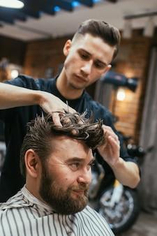 理髪店、ひげを生やした美容師。美しい髪とケア