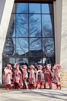 新しいファッションの女の子、ストリートでポーズをとる流行の創造的な服、ピンクのドレスと帽子、民族服