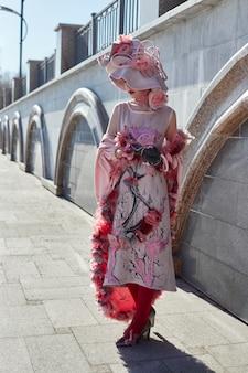 女の子新しいファッション流行の創造的な服は屋外でポーズ、ピンクのドレスと帽子、民族服