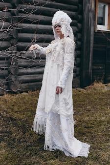 女の子の新しい民族のロシアのファッション流行の創造的な服は古い家、白いドレスと帽子に近いポーズします。
