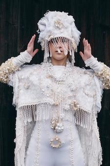 女の子の新しい民族のロシアのファッション流行の創造的な服は古い家、白いドレスと帽子、民族服に近いポーズします。