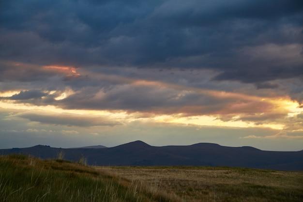 砂漠の夕日、太陽の光が雲の切れ間から輝きます。アルタイのウコク高原