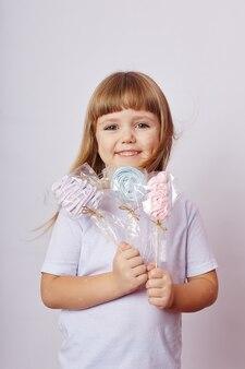 Красивая девушка со светлыми волосами ест леденец, круглую карамель на палочке в руках