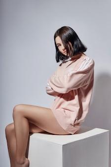 スタジオのホワイトキューブの上に座ってのシャツでファッションのセクシーなブルネットの少女。ファッションポーズ女性の感情