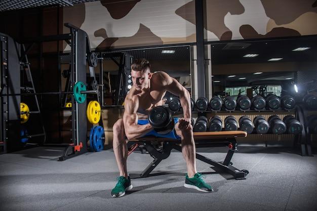 Сексуальный мужчина в тренажерном зале с гантелями. спортивный человек с большими мышцами