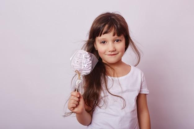 ブロンドの髪を持つ美しい少女は、ロリポップ、手でスティックに丸いキャラメルを食べる