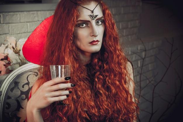 ハロウィーンの女性魔女は、死者の祭りの準備をしています。赤髪の女性の黒魔道士