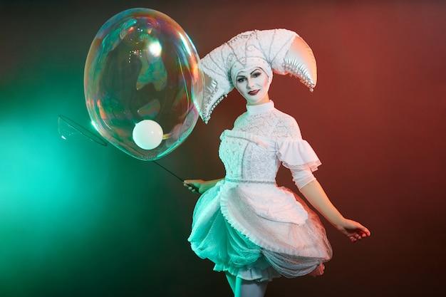 サーカスのパフォーマーのマジシャンがシャボン玉でトリックを披露します。女性と少女がシャボン玉を膨らませる