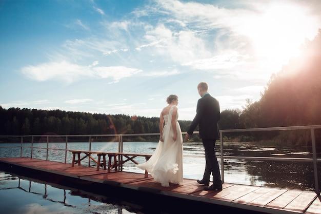 新郎新婦が湖の橋の上に立っています。カップルの新婚夫婦