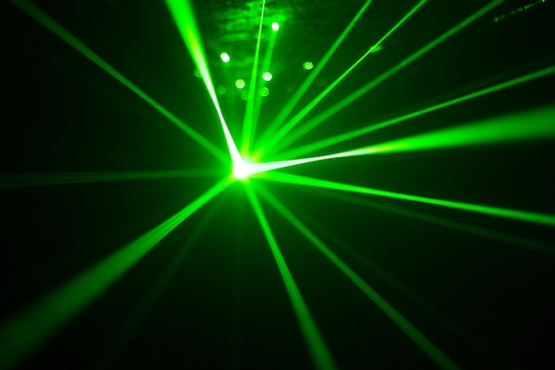 Зеленый и красный лазер в ночном клубе. лазерные лучи на темном фоне, клубная атмосфера