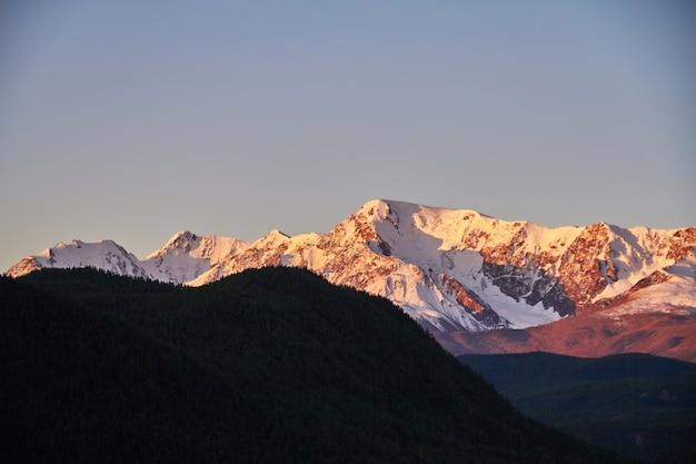 Алтай, заснеженные горы на закате. вечернее солнце светит в горах, осенний пейзаж алтая. шум и размытие
