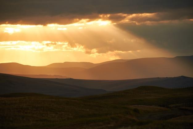 砂漠の夕日、太陽の光が雲の切れ間から輝きます。アルタイのウコク高原。素晴らしい寒い風景