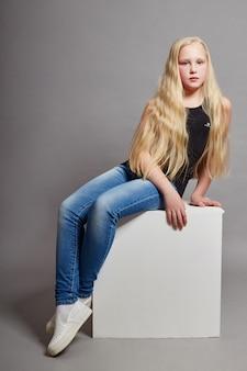 ホワイトキューブの上に座って、ポーズのカジュアルな服装で長い髪のファッションの女の子。美しい若い子