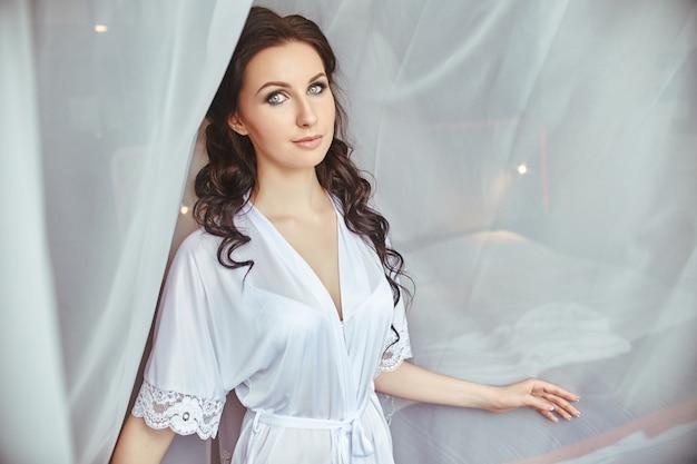 Утро невесты, девушка в шелковом халате стоит у окна на фоне белых занавесок