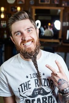 現代の男性ヒップスターのヘアカット、長い髪を持つ男性に最適なヘアスタイル。髪サロンでレトロな散髪