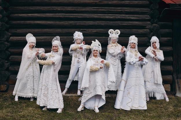 女の子の新しい民族のロシアのファッション流行の創造的な服は古い家、白いドレスと帽子、民族服、ロシアのファッションに近いポーズします。仮装、若い女の子が一緒。 、