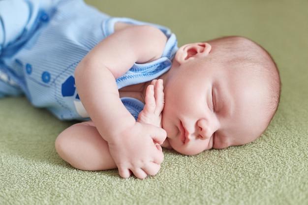 生まれたばかりの赤ちゃんはソファに横になっています。赤ちゃん