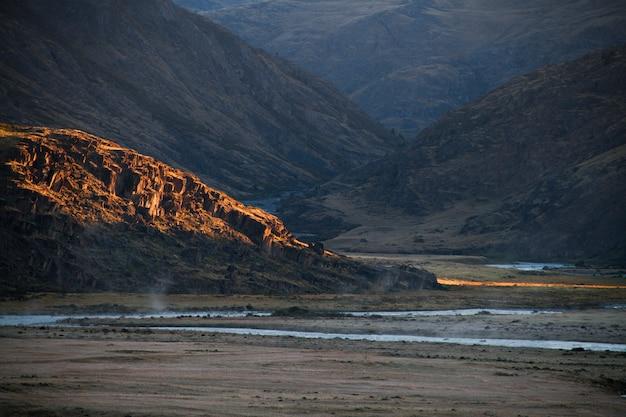 砂漠の夕日、太陽の光が雲の切れ間から輝きます。アルタイのウコク高原。素晴らしい寒い風景。誰もいない
