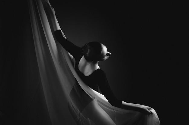 ロシア、モスクワ、:黒と白の布でポーズをとる女性の体操選手。女性の体操選手のアート写真。白黒写真