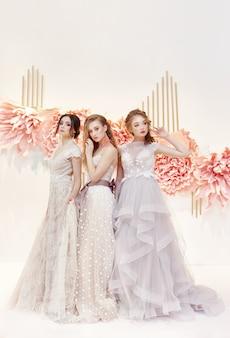 高価なウェディングドレスの美しいトリオ花嫁