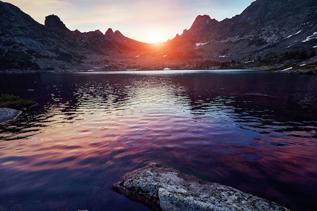 Красивое озеро в горах в вечернем солнце. закат в сказочных горах, озеро образовано каменным обвалом