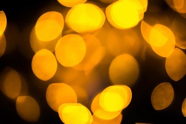 黒の背景にぼやけた色ボケ。暗闇の中で輝くボケライト、反射
