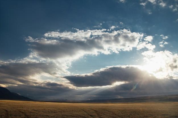 砂漠の夕日、太陽の光が雲の切れ間から輝きます。アルタイのウコク台地