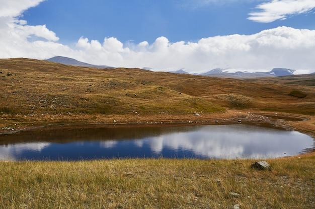 草原の小さな湖は、山々の間に落ちます。アルタイのウコク高原。素晴らしい寒い風景