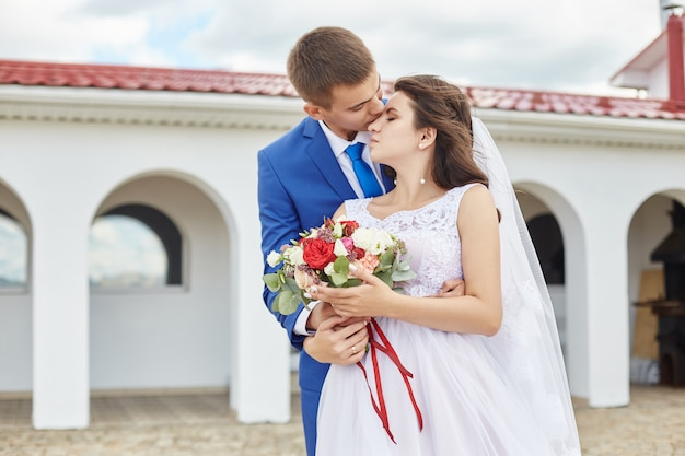 Молодожены обнимаются и целуются возле маяка на свадьбе