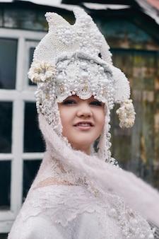 女の子の新しい民族のロシアのファッション流行の創造的な服は古い家の近くにポーズします。