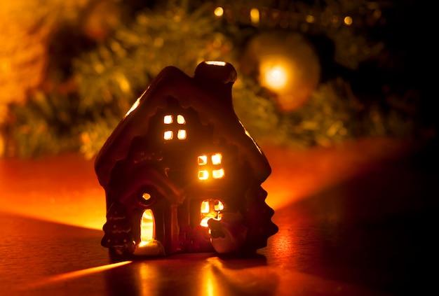 燃える光の中の小さなおもちゃのクリスマスハウス