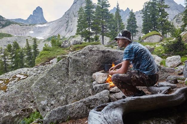男は自然の森でキャンプファイヤーを構築します