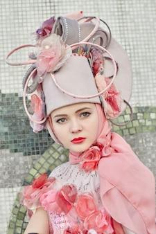 女の子の新しいファッション流行の創造的な服は屋外でポーズ、ピンクのドレスと帽子
