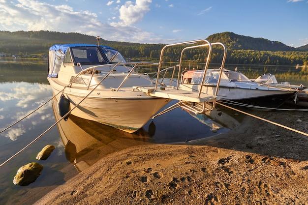 Лодка на озере на фоне заката в ясный летний день.