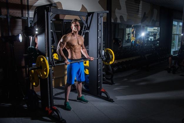 大きな筋肉とジム、フィットネス、腹部圧迫で腹筋運動の広い背筋を持つスポーティな男。