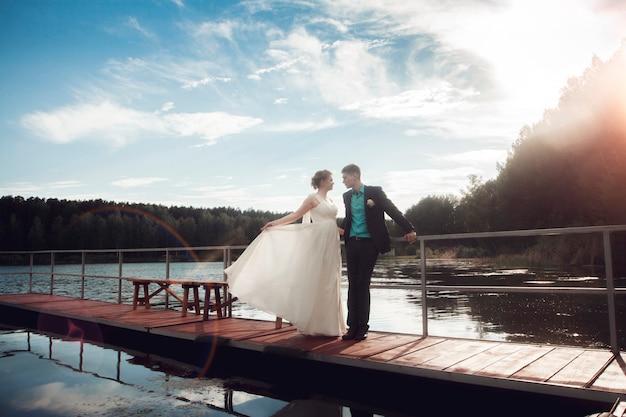 新郎新婦が湖の橋の上に立っています。